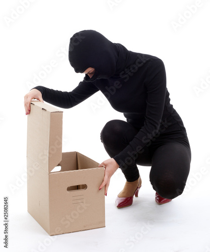 thief in black clothes and balaclava with box