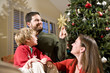 Family with child by Christmas tree