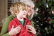 Boy sitting on grandmother's lap by Christmas tree