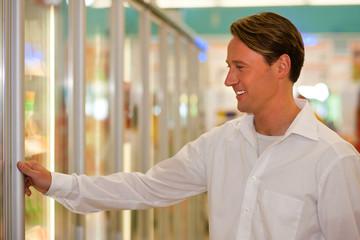 Mann im Supermarkt Tiefkühlabteilung