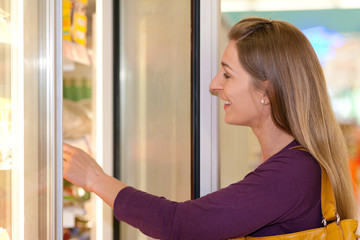 Frau im Supermarkt Tiefkühlabteilung