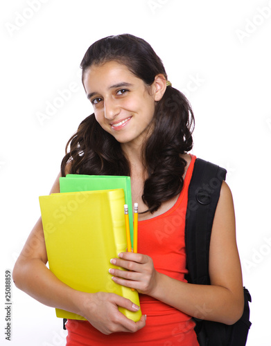 School Girl posing while holding books and backpack