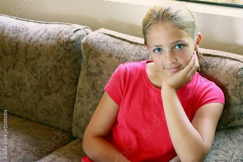 Young girl with red blouce sitting brown couch.