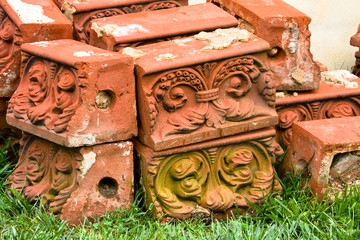 Antique molded bricks stacked on grass.