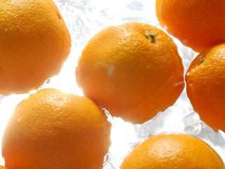 Oranges splashing in water