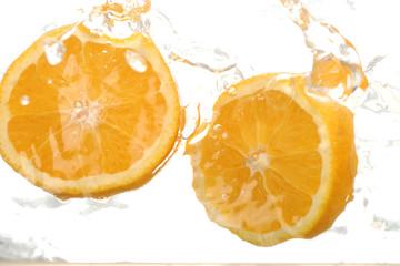 Two orange halves splashing in water