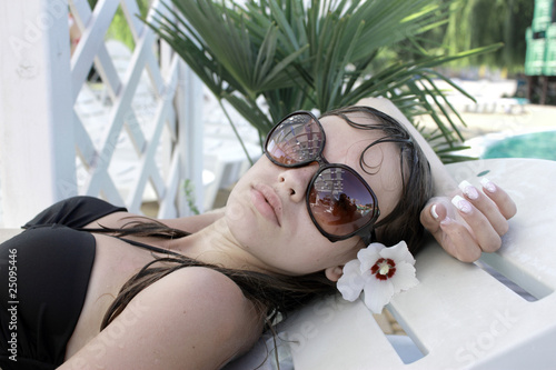 girl in sun glasses has a rest near pool