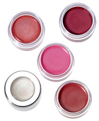 Multy-colored lip gloss in round silver plastic containers on wh