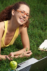 Young Women with laptop on a meadow