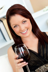 Elegant young woman holding a glass of wine at home