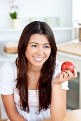 Radiant asian woman holding an apple in the kitchen