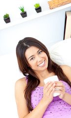Pretty asian woman holding a cup of coffee at home