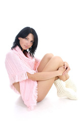 attractive brunette in pink sweater sitting over white