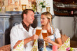 Paar in Tracht trinkt Weißbier