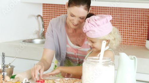 mother and cute daughter making cookies for christmas