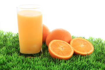 Orange juice and fruit on grass