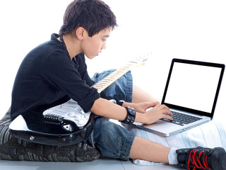 boy with guitar typing on notebook computer isolated on white