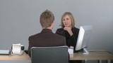 Two associates talking at a desk