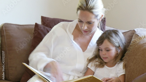 Loving Mother with curious daughter reading a book