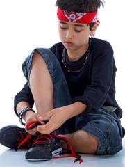 child tying his shoe laces isolated on white background