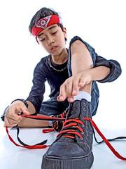 boy tying his shoe laces isolated on white background
