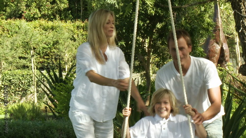 Happy Parents help their son on a swing