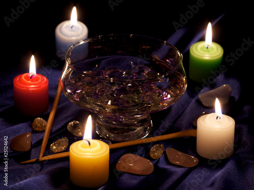 burning candles, cup with water, crystals, stones and two batons