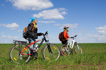 Two girls on bicycles in the countryside.