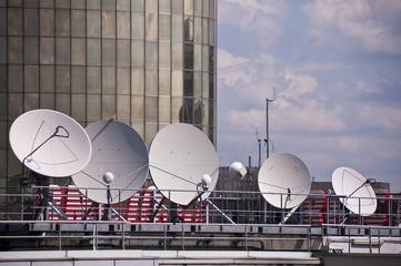 Plusieurs antennes paraboliques sur le toit d'un immeuble
