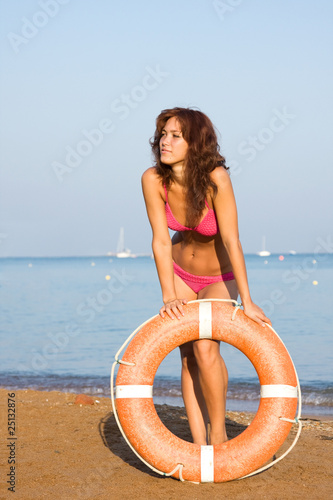 A young girl with a Life Ring on the beach