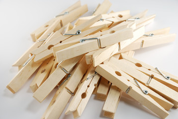 The wooden clothespin pile up on the white background