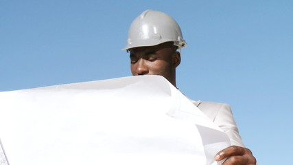 responsible businessman looking at a blueprint outside