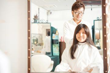 鏡に映った髪を切られる女性