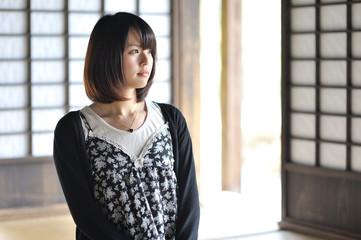 和室に座り外を見てる女性