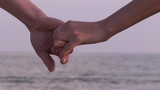 close up of a couple holding hands looking the sea
