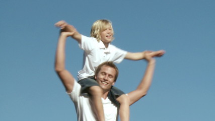Athletic father with his son on his shoulders outside