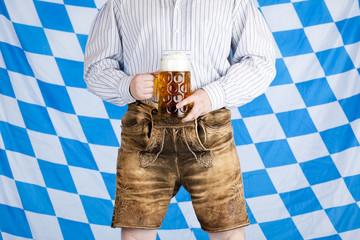 Bayerischer Mann in Lederhose hält Oktoberfest Maß Bier