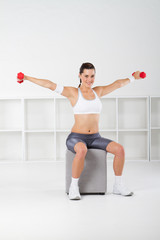 pretty fitness woman lifting weights