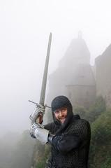 Siegessicherer Ritter vor nebeliger Burg
