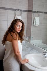 dressed in towel beautiful woman staying at modern bathroom