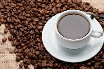 Cup of coffee on coffee grains