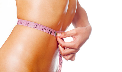 Slim woman measuring waist isolated