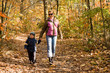 Mother and son taking a walk in autumn forest