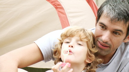 father and son doing soap bubbles during camping