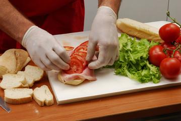 Manos preparando sandwitch.