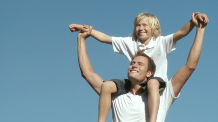 Athletic Father with his son on his shoulders pivoting