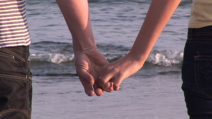 close-up of a couple holding hands on the beach