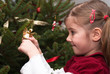 Cheerful little girl view the ornaments of a Christmas tree