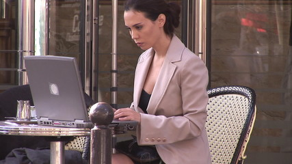 businesswoman at a cafe working with laptop