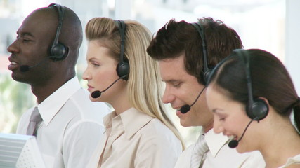 women and men working in a call center with headphones on